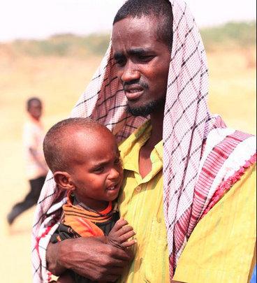 Somali man with baby at Dadaab refugee camp