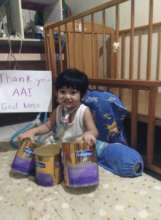 Child at PSOD with nutrition supplements from AAI