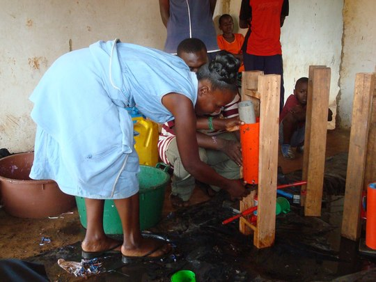 Woman learning how to use a briquette press