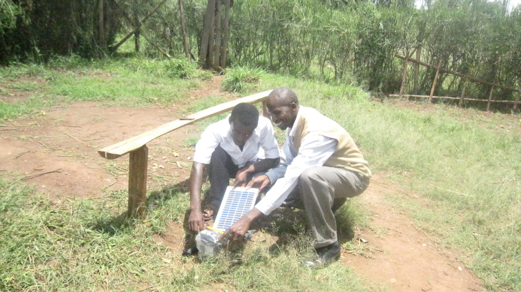 Henry and a student installing solar lights