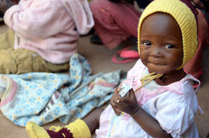 A young girl eats Plumpy'Nut at a health clinic