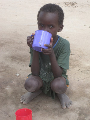 This boy is happy to have a cup to drink water.