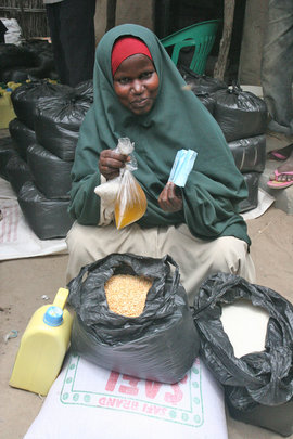 A woman receives rice, beans, oil, sugar and salt