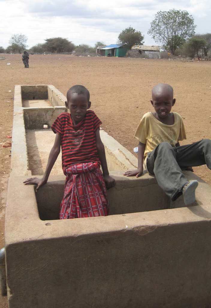 Kids play in a dry trough.