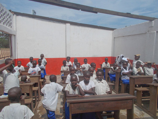 Roofless students endure extreme heat in class.