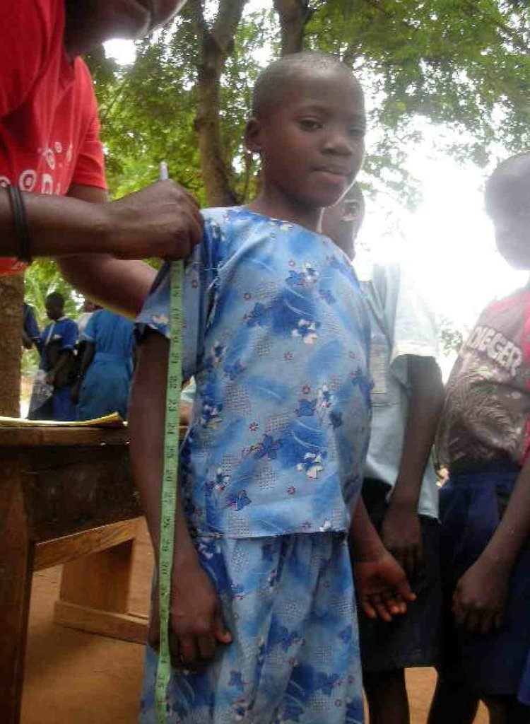 Local tailor takes measurements for school uniform