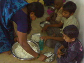 Cook serving midday meal at Prashant Nagar Colony