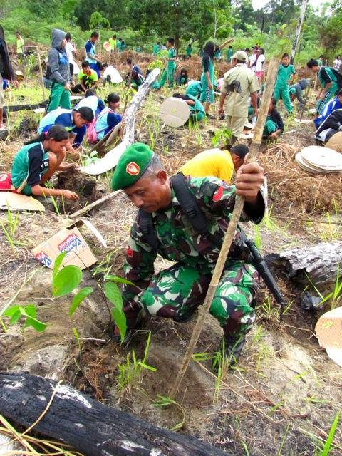 Participants in Green Day plant seedlings together