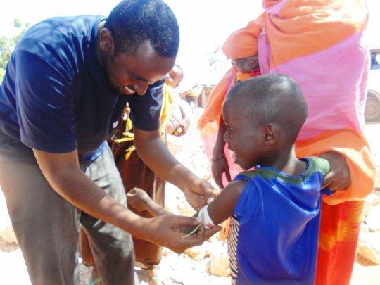 RI staff member screening a child for malnutrition