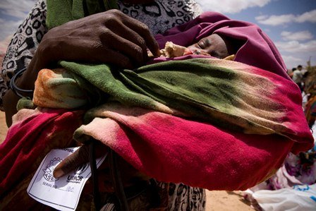 A mother holds her baby while awaiting UNHCR aid.