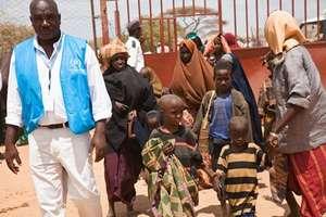 UNHCR staff brings a family into reception center