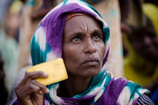 A Somali woman shows her UNHCR card to receive aid