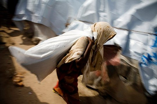 A woman collects her UNHCR aid package in Somalia.