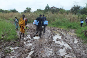 Health workers carry supplies, Boma