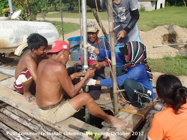 Pulili locals installing submersible water pump