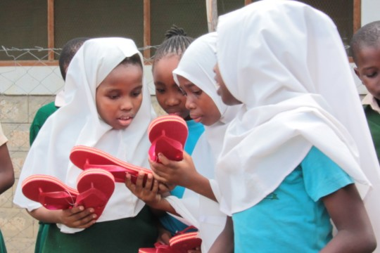 Children investigating new slippers from Rotary