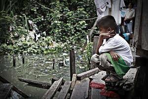 Boy next to slum house