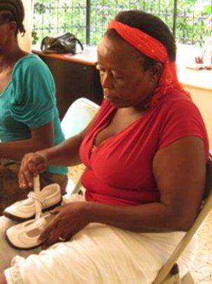 KOFAVIV outreach worker putting aside shoes