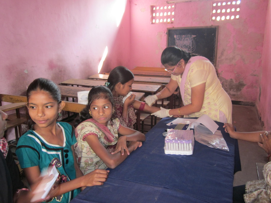 Girls give blood samples at Health Camp