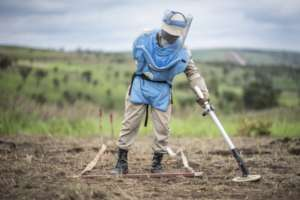 A deminer searches the field in Angola