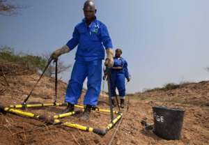 Deminers using a large loop detector at Malhazine