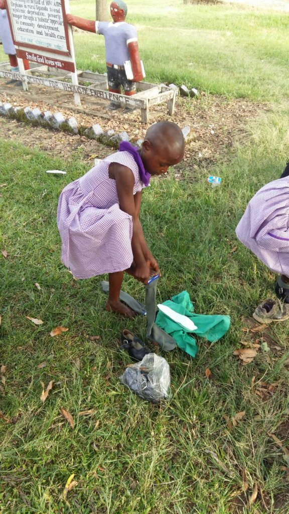 Primary student putting on the shoes you gave her