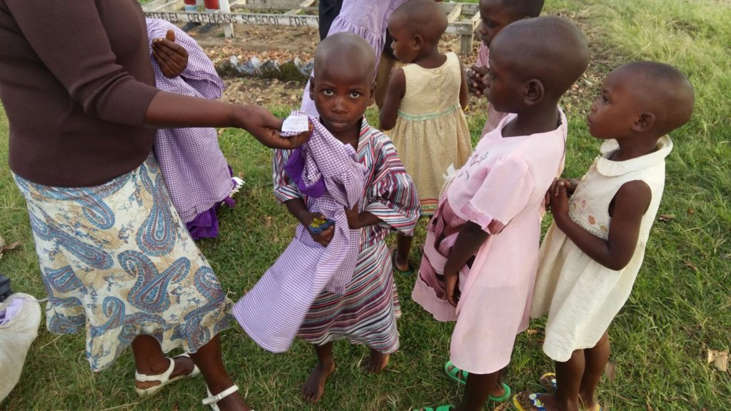 Nursery students putting on the uniforms you gave
