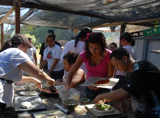 Youth making pizza from ingredients they harvested
