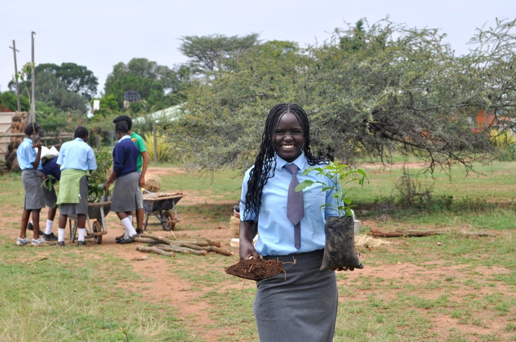 """""Give Green"""" captures Form IV student Florence helping to plant fruit and vegetables that are grown organically on campus.  Daraja started a permaculture garden the year after the school opened with the goal of providing food for the school as well as cutting food costs in half."