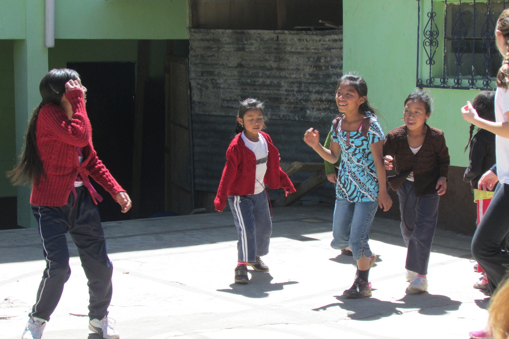 Girls playing soccer in front of the school