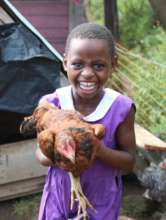 Nyaka student playing with chicken on Desire farm