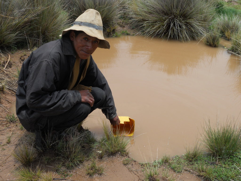A villager collects water from the current source.