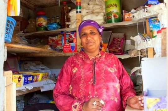 A B'edaya mother stands in front of her store