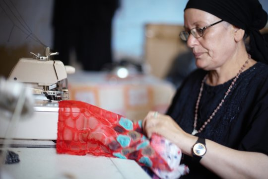 A mother sewing as part of her B'edaya project