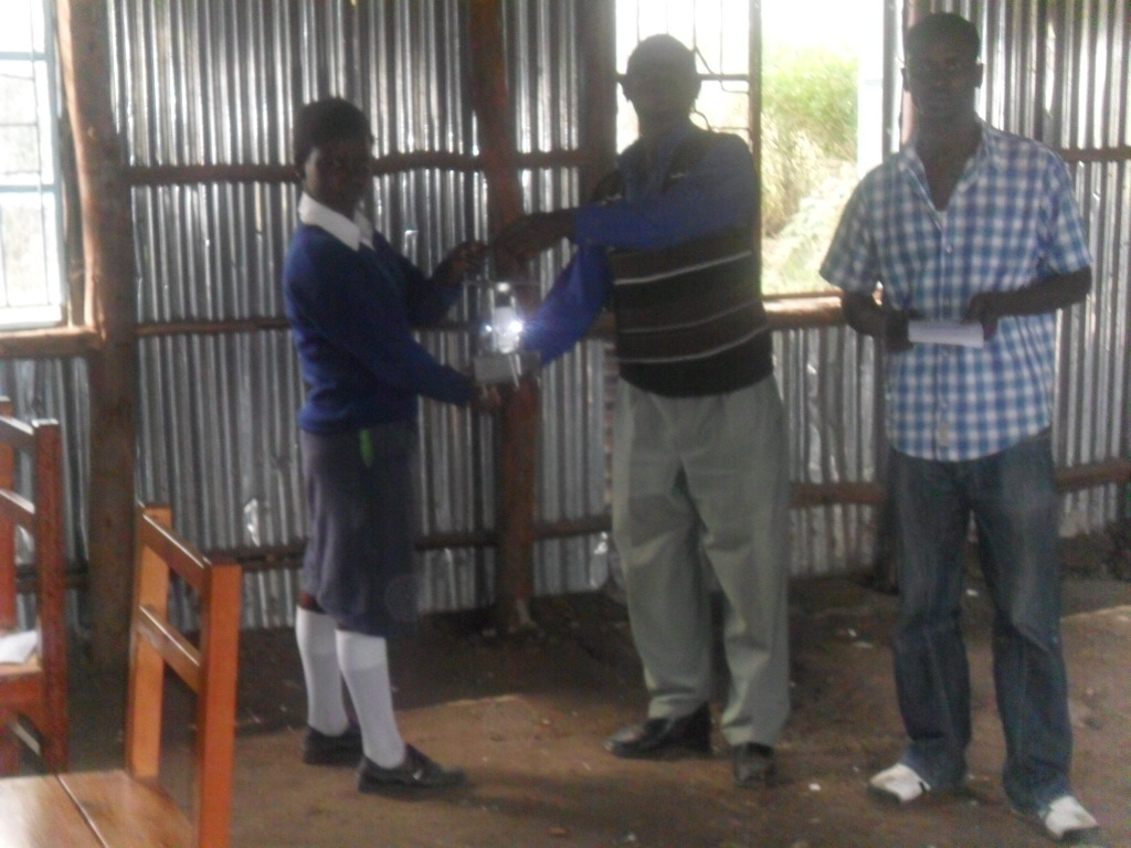 A student receiving a lamp in Makutano