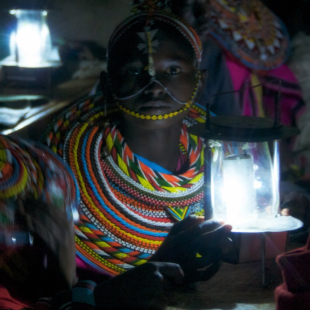 Nashaki one of the beneficiaries of our solar project holds our mwangabora lamp in the class at night. She is able to study at night after taking care of her fathers animals during the day using our solar lamps that we have distributed to school.