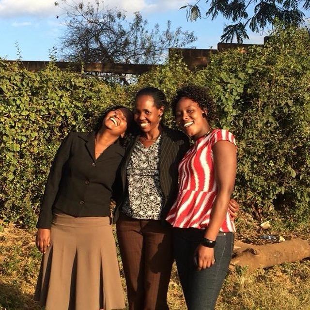 Alumnae laugh with MGEF Kajiado staff Member