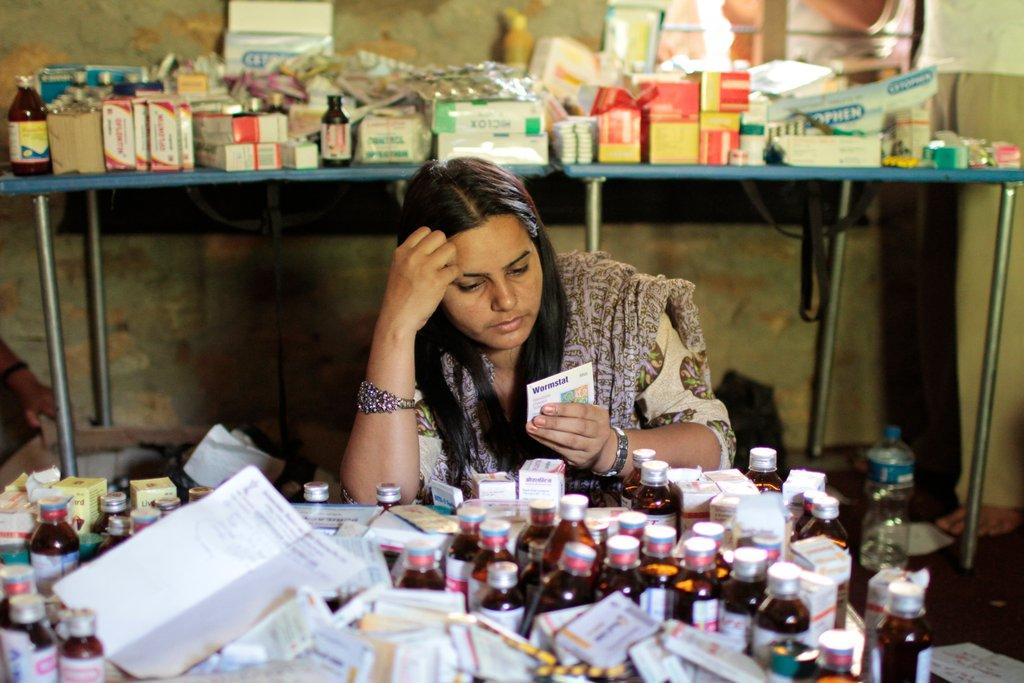 Volunteer Nepali nurse with medicine at camp