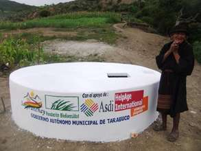 An older woman with her community's new water tank