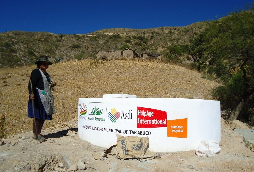 Older Bolivian woman at new community water tank