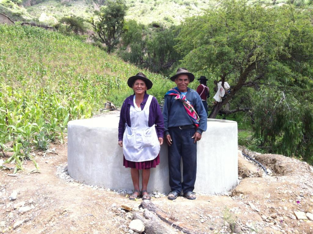 Older farmers with one of water tanks built