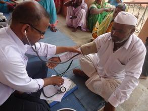 Dr. Reddi taking blood pressure of local farmer