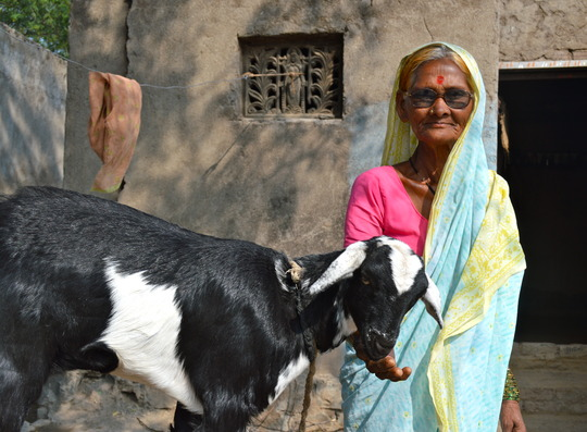A village woman proudly stands with her goat
