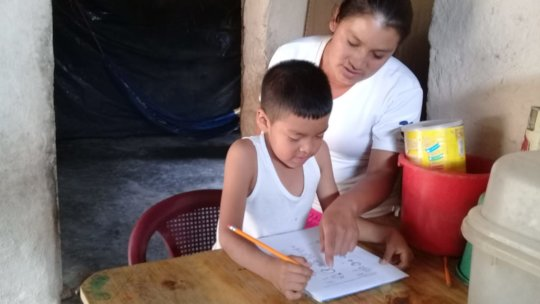 Child learning from home with the help of his mom.