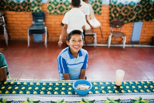 A student enjoys school lunch in Las Sabanas