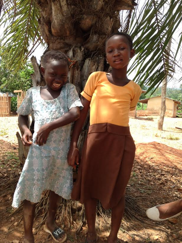 two young sisters stand next to each other smiling