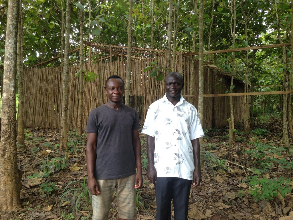 Graduate Samuel (right) in front of cropping house