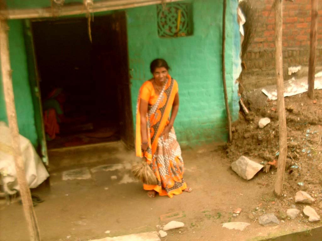 Kamal sweeping the courtyard of her house