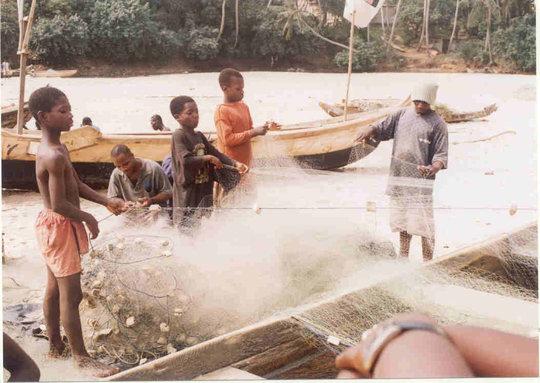 Children mending fishing nets at the beach