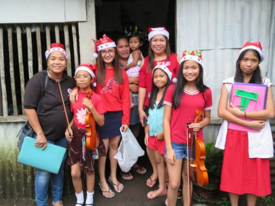 Mercy In Action midwife team and family caroling